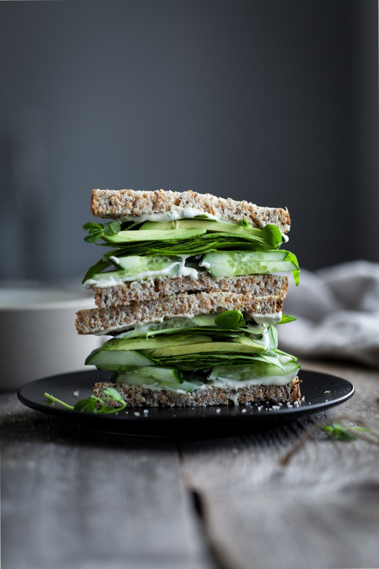 Green vegetable sandwich with mayonnaise and whole wheat bread, stacked.
