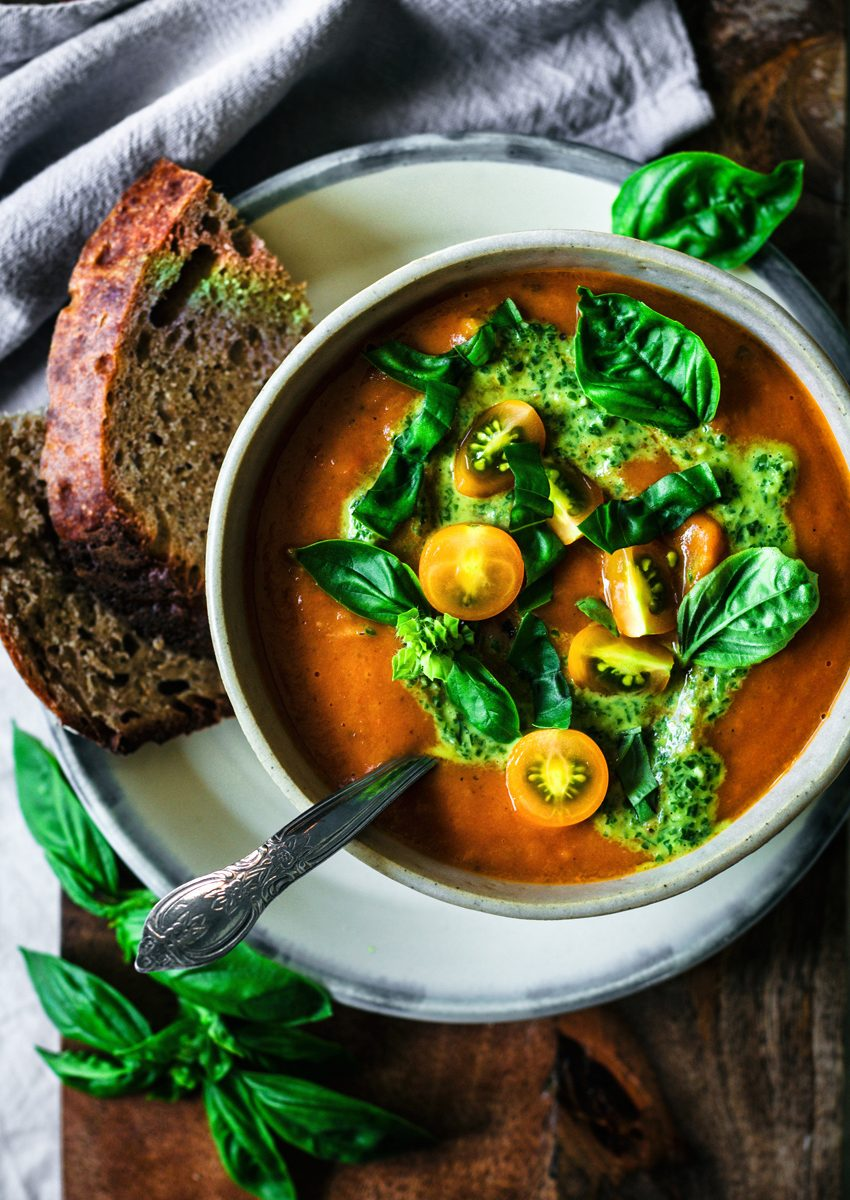Tomato soup in bowl with pesto, orange cherry tomatoes, and basil.