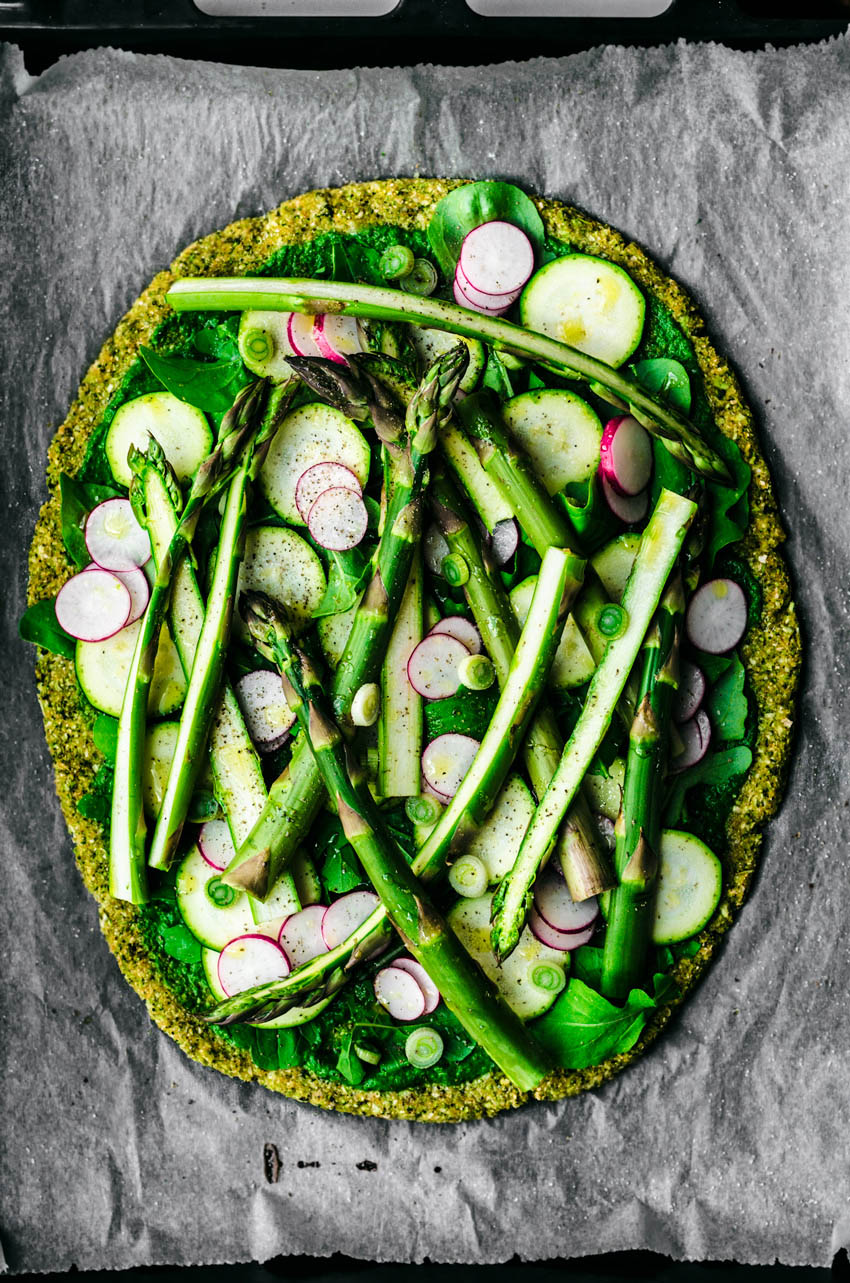 Broccoli pizza crust topped with asparagus, radishes, zucchini, greens, spring onion, and pesto.