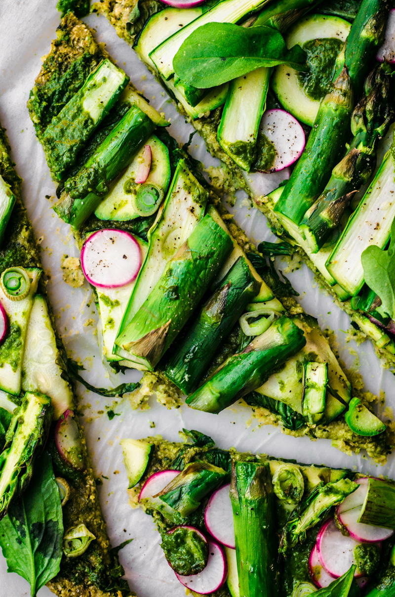 Broccoli flatbread topped with asparagus, radishes, zucchini, greens, spring onion, and pesto cut into irregular slices.