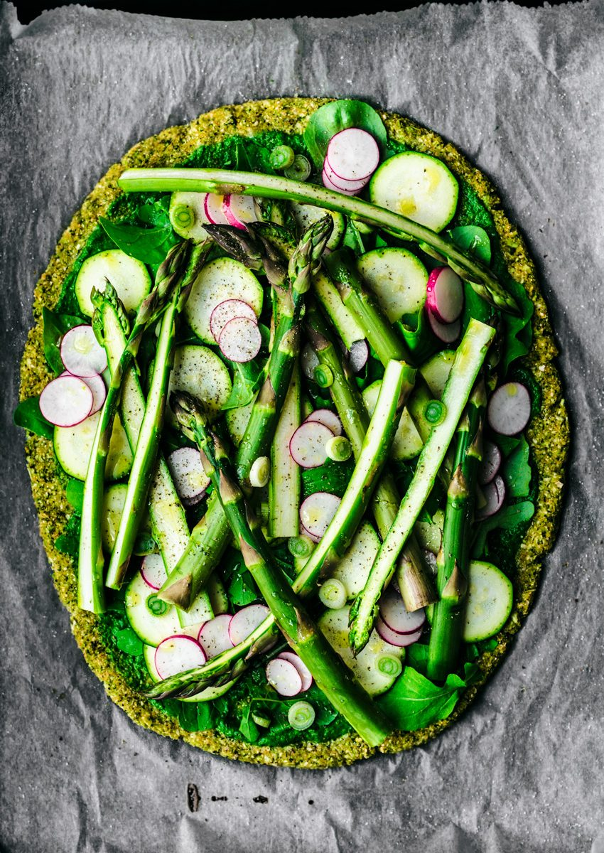 Broccoli flatbread topped with asparagus, radishes, zucchini, greens, spring onion, and pesto.