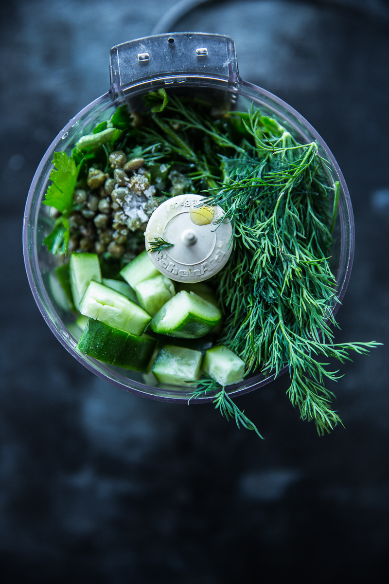 Cucumber, herbs, and capers in small food processor on dark background.