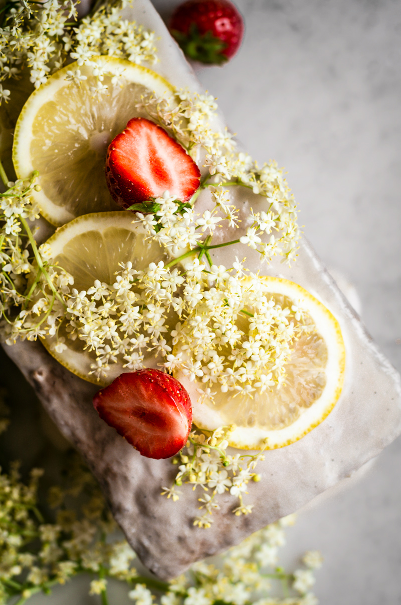 Lemon elderflower cake topped with a glaze, lemon slices, elderflower, and strawberries.