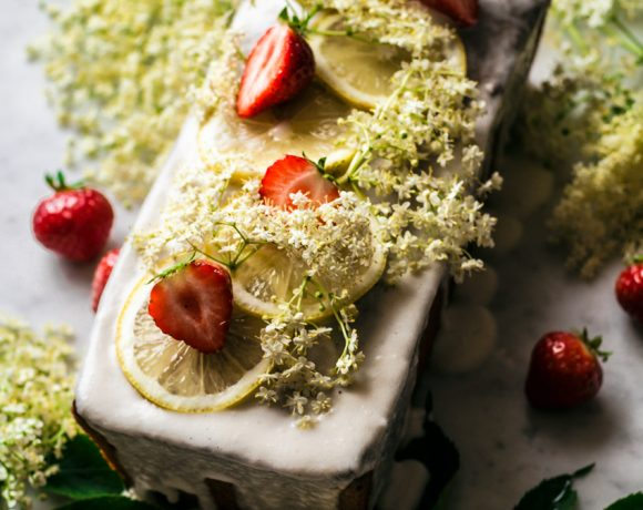 Lemon elderflower loaf cake topped with a glaze, lemon slices, elderflower, and strawberries.