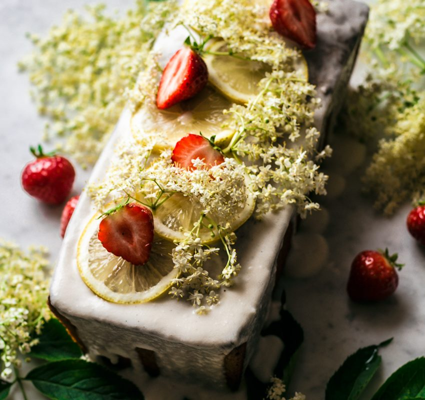Lemon elderflower loaf cake topped with a glaze, lemon slices, elderflower, and strawberries.