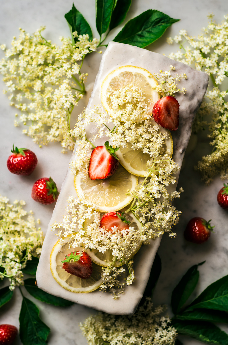 Loaf cake topped with a glaze, lemon slices, elderflower, and strawberries.