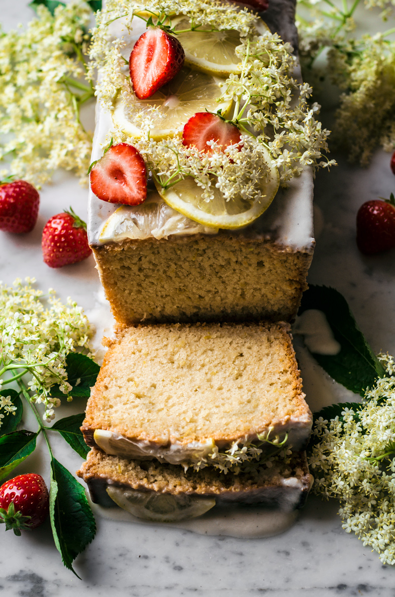 Loaf cake topped with a glaze, lemon slices, elderflower, and strawberries, sliced.