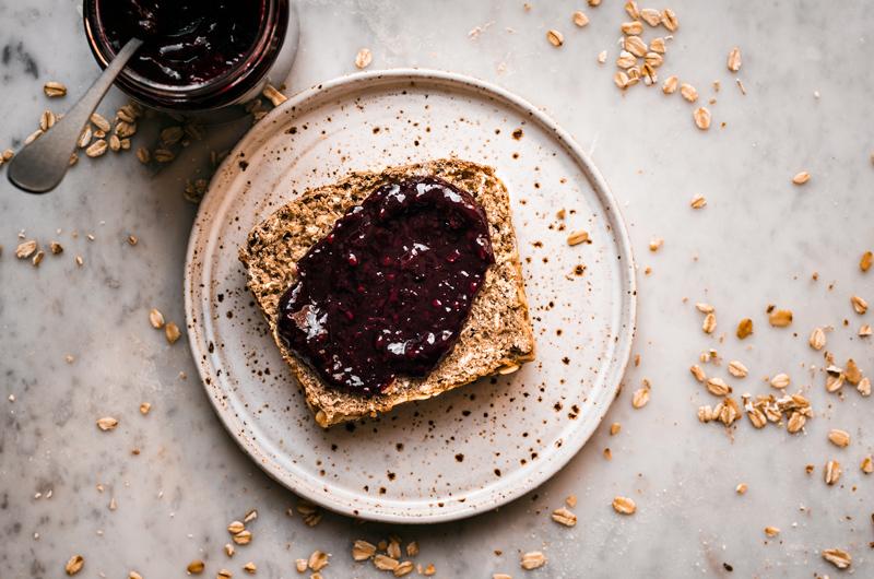 Honey oat bread slice on speckled plate with blackberry jam.