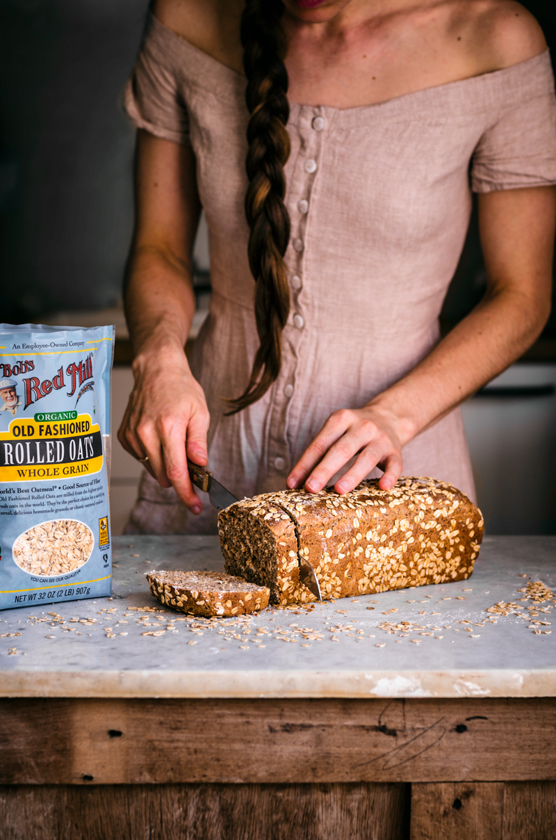 Woman in dress cutting honey oat bread with bag of oats to the left.
