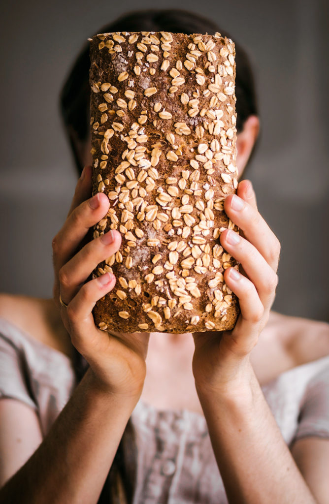 Woman holding honey oat bread in front of her face, top out.