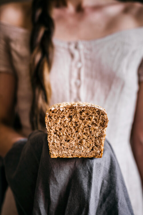 Woman holding loaf of bread, sliced side forward.