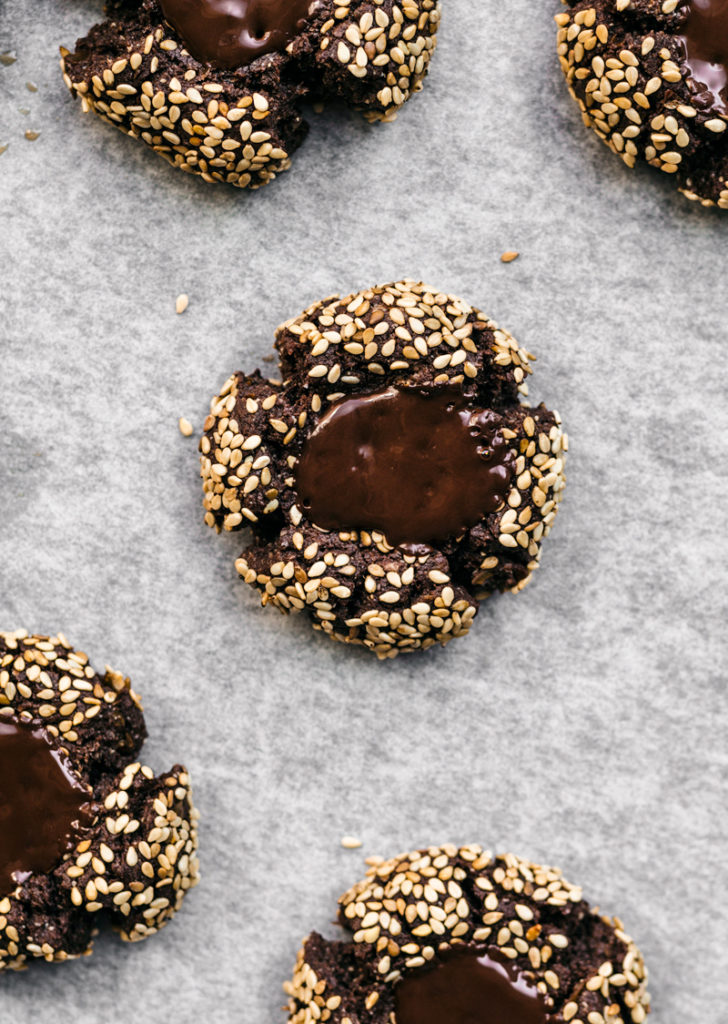 Chocolate thumbprint cookies with sesame seeds and melted chocolate centre.
