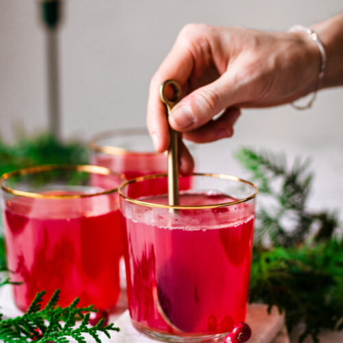 Hand stirring a spoon in a glass of bright red tea.