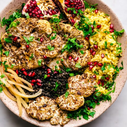 Roasted cauliflower steaks in a large bowl with preserved lemon, pomegranate, saffron rice, and black lentils.