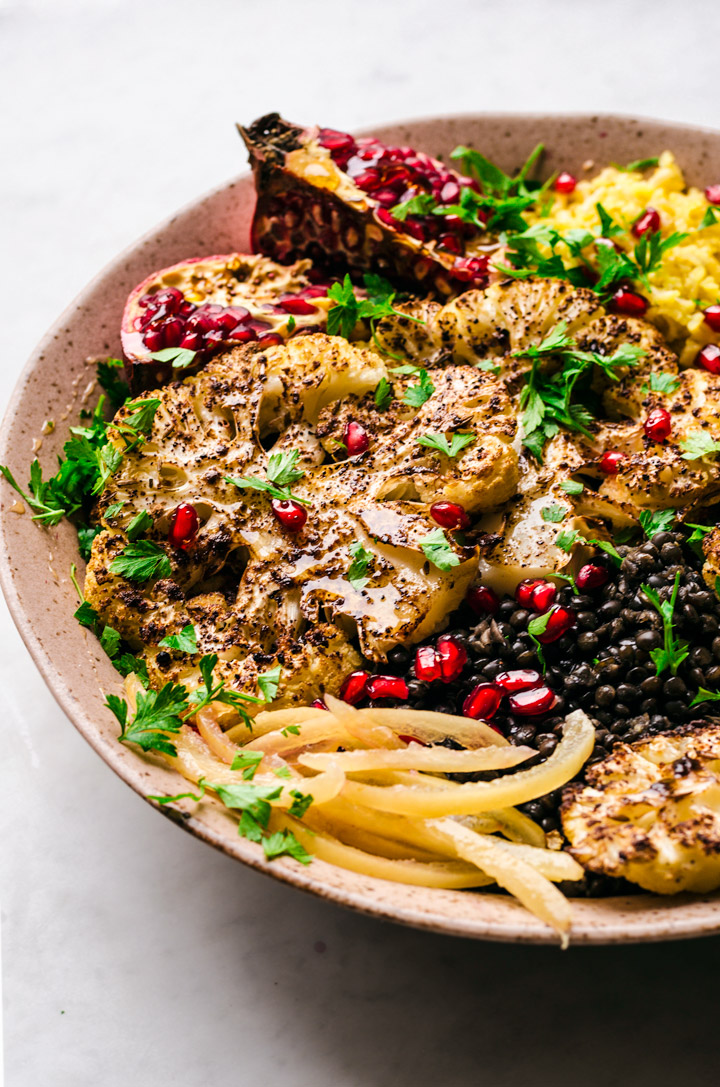 Roasted cauliflower steaks in a large bowl with preserved lemon, pomegranate, and black lentils.