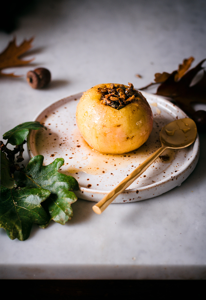 Stuffed baked apple on a speckled plate with a spoon.