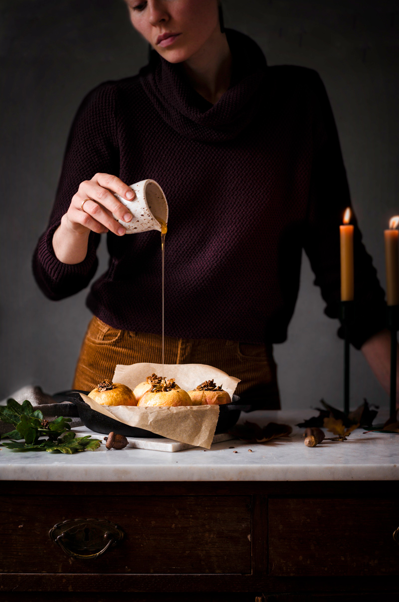 Woman pouring maple syrup onto stuffed baked apples in a pan.