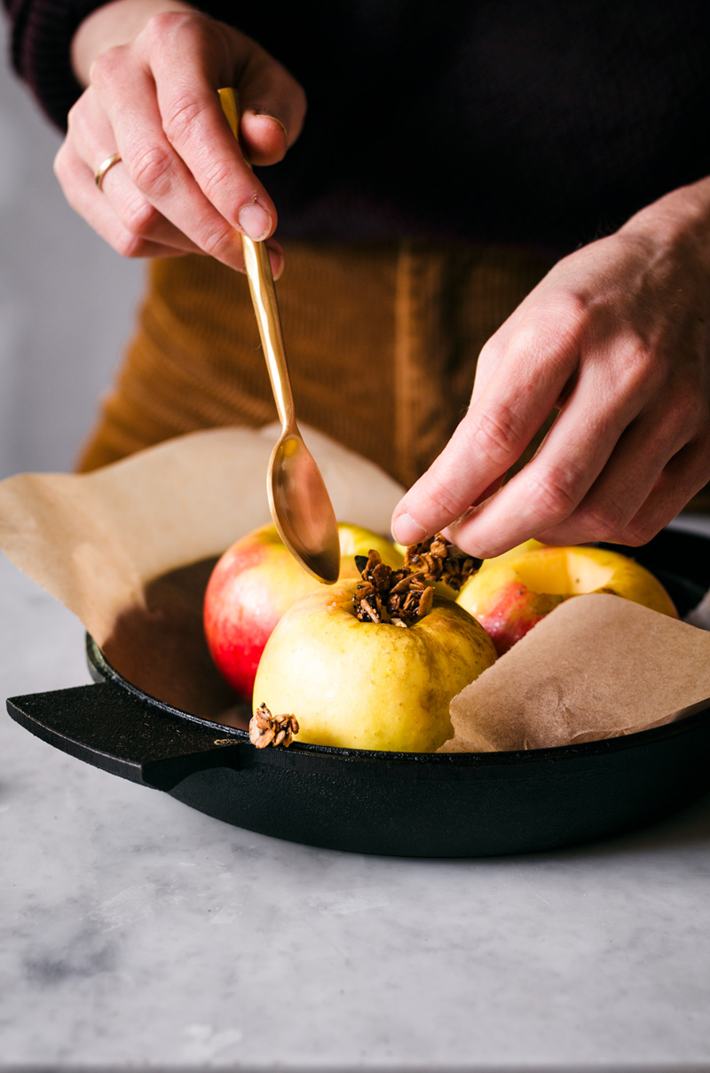 Woman's hands adding granola to cored apples.