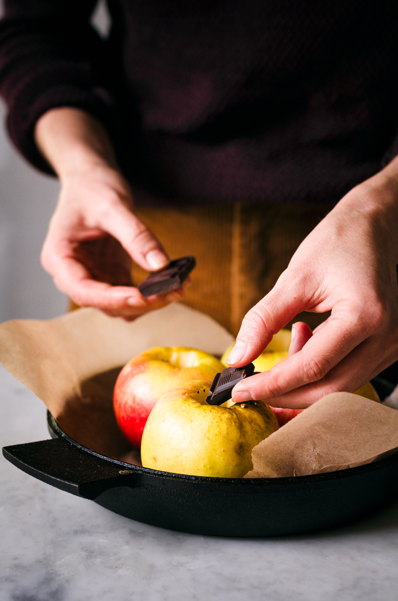 Woman's hands adding chocolate squares to cored apples.