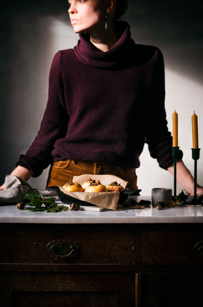 Woman standing behind scene with baked apples on a counter.