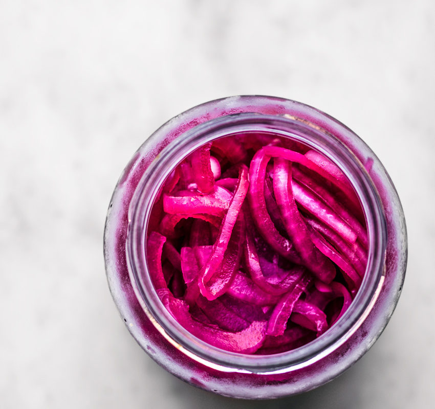 A jar of bright pink pickled red onions, top down view.