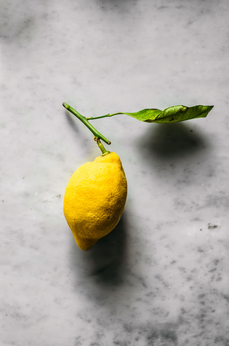 Single lemon with leaf attached.
