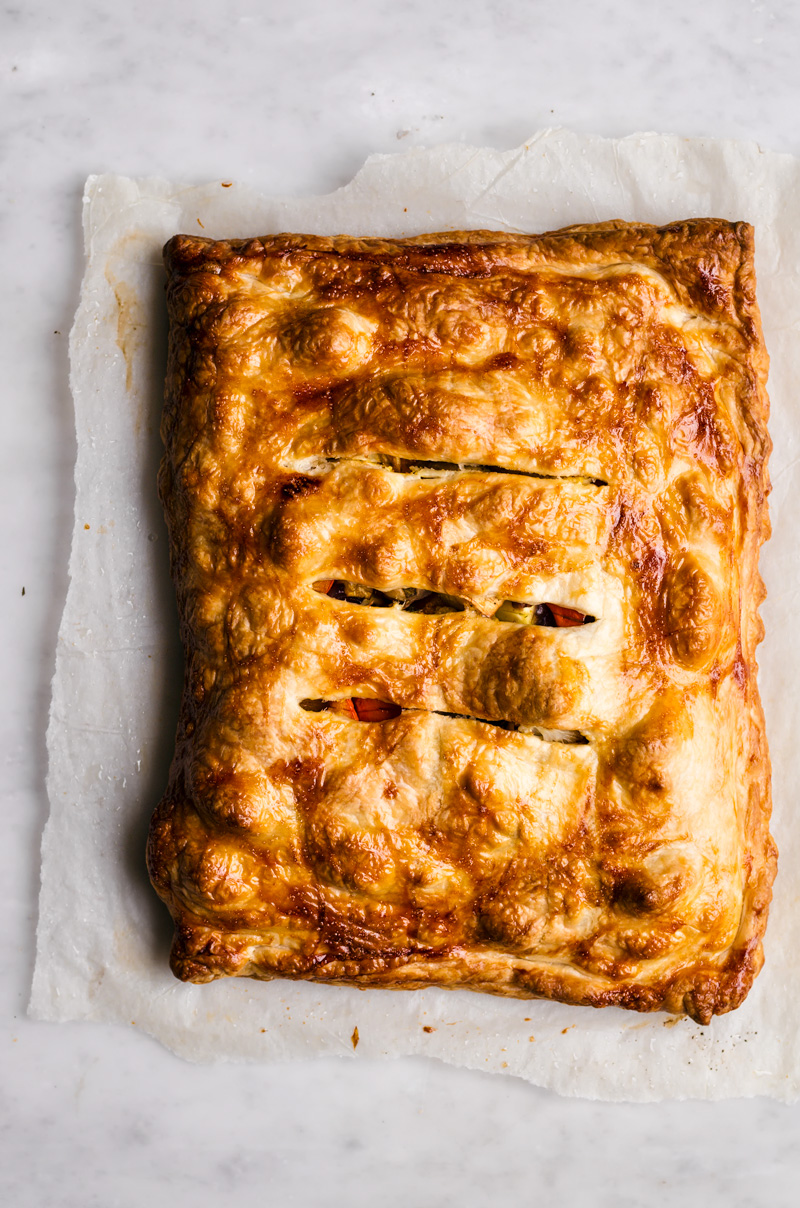 Roasted vegetable pie in puff pastry, three cuts across the top.