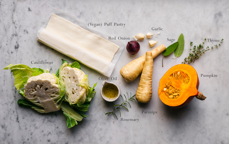 Ingredients for a roasted vegetable pie on a marble background.