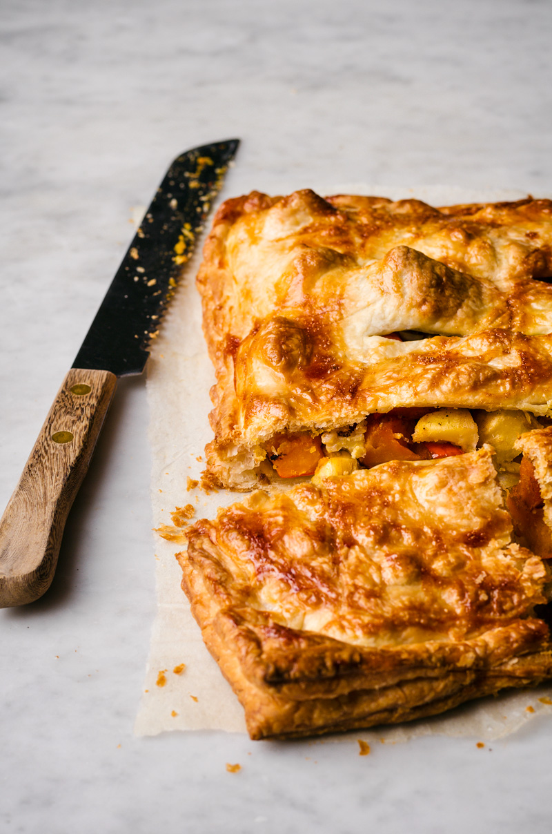 Puff pastry pie filled with roasted winter vegetables, inside view, knife alongside.