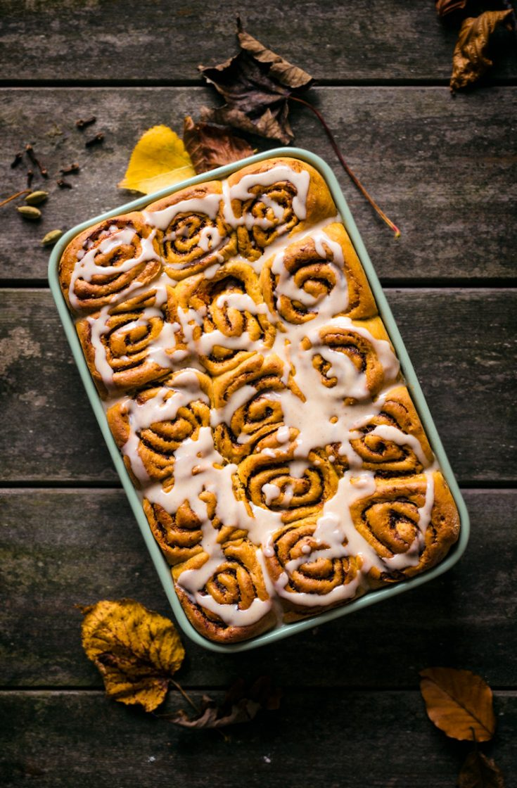 Glazed pumpkin cinnamon buns on a wooden background.