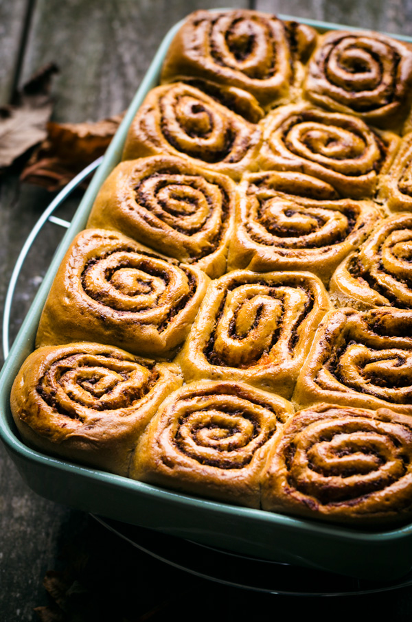 Pumpkin cinnamon rolls in baking dish on cooling rack.