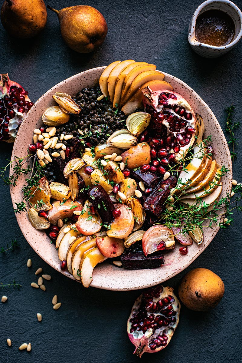 Lentil salad with beets, shallots, pomegranate, and pears in a large pink bowl.
