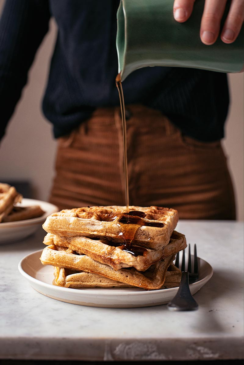 Woman pouring maple syrup onto a stack of waffles.