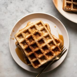 Stack of waffles with maple syrup, top down view.