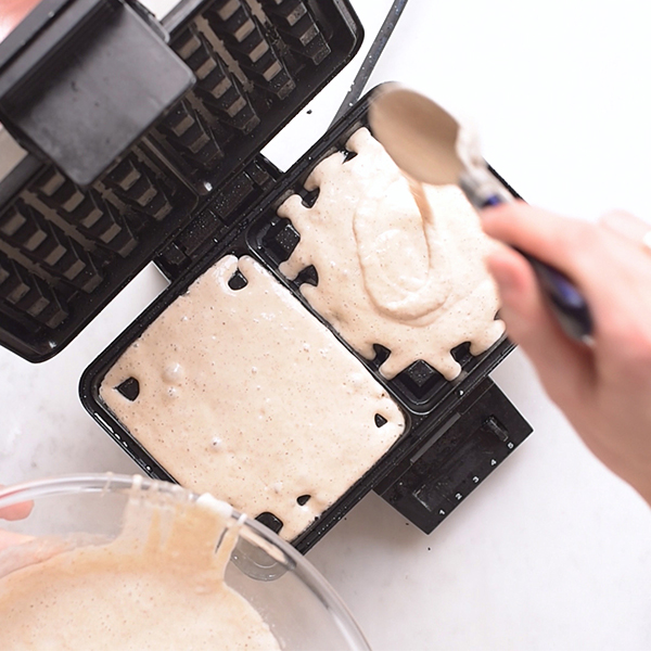 Sourdough waffle batter being poured into a waffle iron.