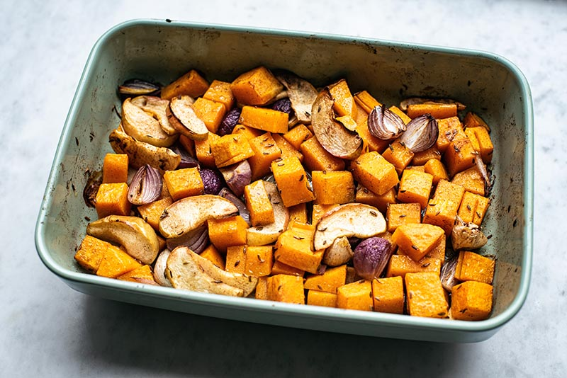 Tray of roasted winter vegetables and apples.