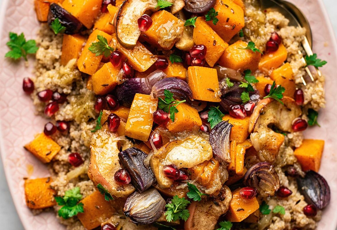Moroccan spiced quinoa salad with butternut squash, red onion, and apples on pink platter.