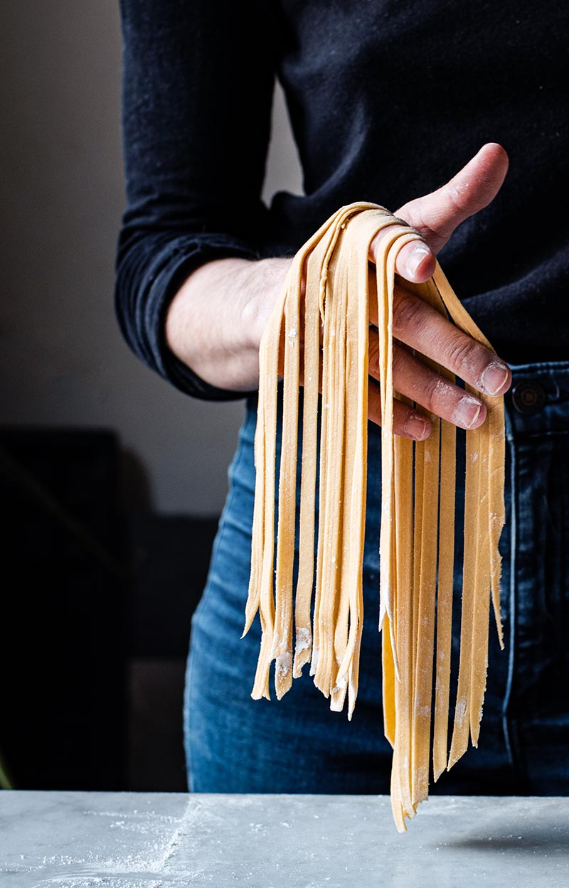 Woman holding fresh tagliatelle in one hand.