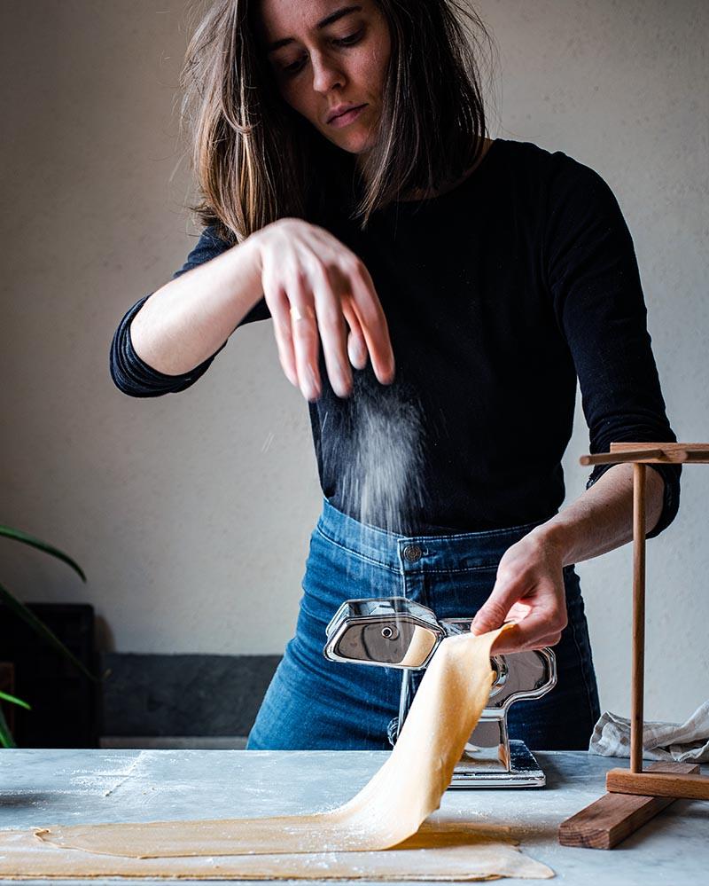 Woman making kamut pasta with a pasta machine.