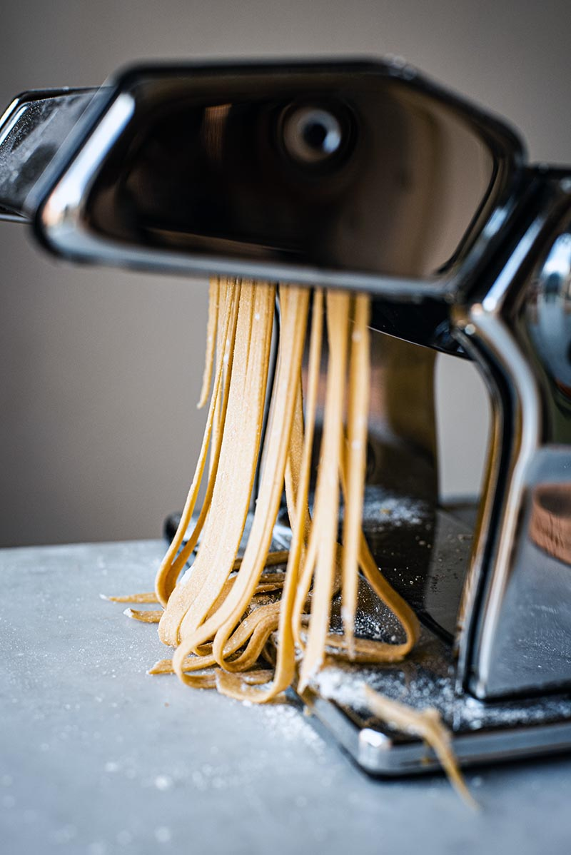 Close up of tagliatelle coming out of pasta machine.