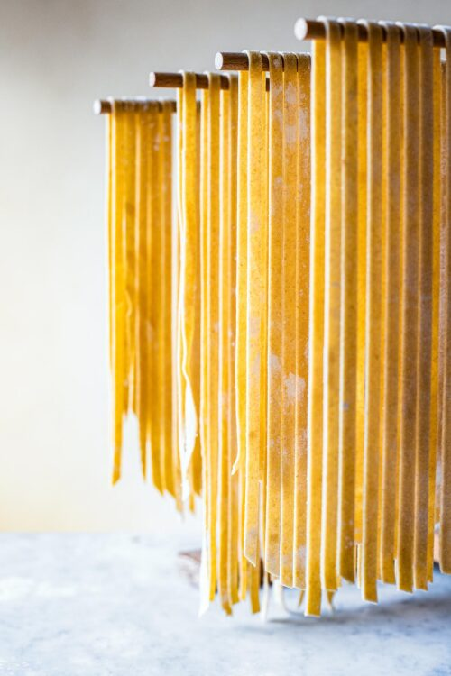 Kamut pasta cut into tagliatelle drying on a wooden wrack.