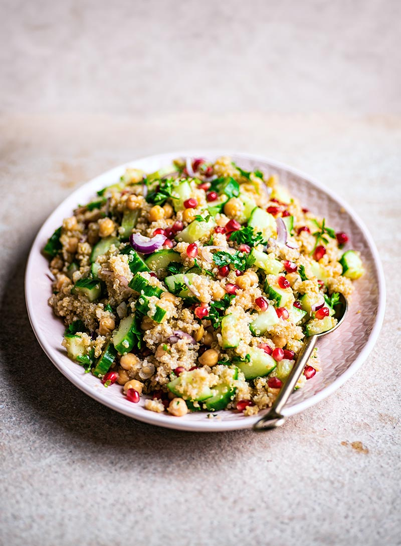 Pink platter with a chickpea quinoa salad with cucumber, pomegranate, and herbs, front view.
