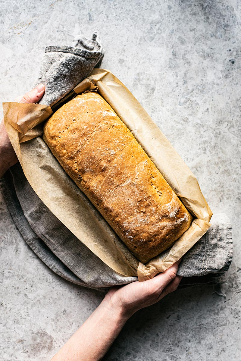 Hands holding a loaf of bread in tin lined with parchment paper.