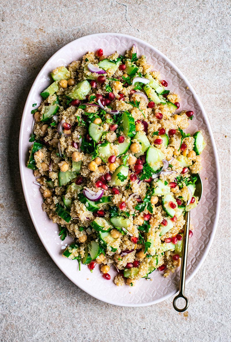 Top view of quinoa salad with chickpeas, vegetables, and pomegranate on a pink platter.