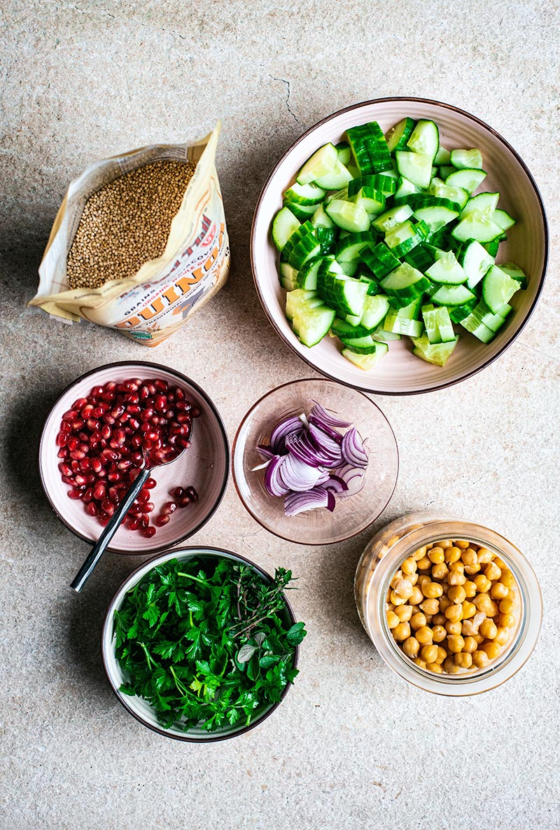 Ingredients for quinoa salad. Dried quinoa, chopped cucumber, red onion, parsley, pomegranate, and cooked chickpeas.