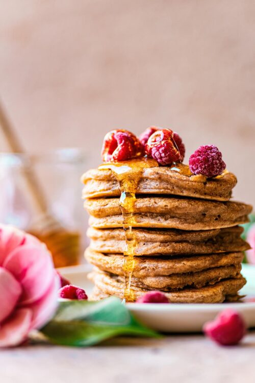 Stack of American style pancakes topped with frozen raspberries and syrup.