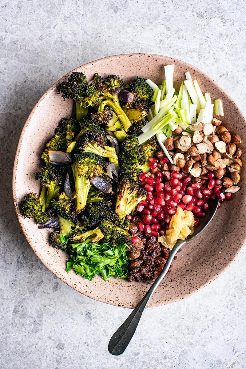 Top view of vegan broccoli salad ingredients - roasted broccoli and onion, raw stems, pomegranate, raisins, herbs, and nuts.