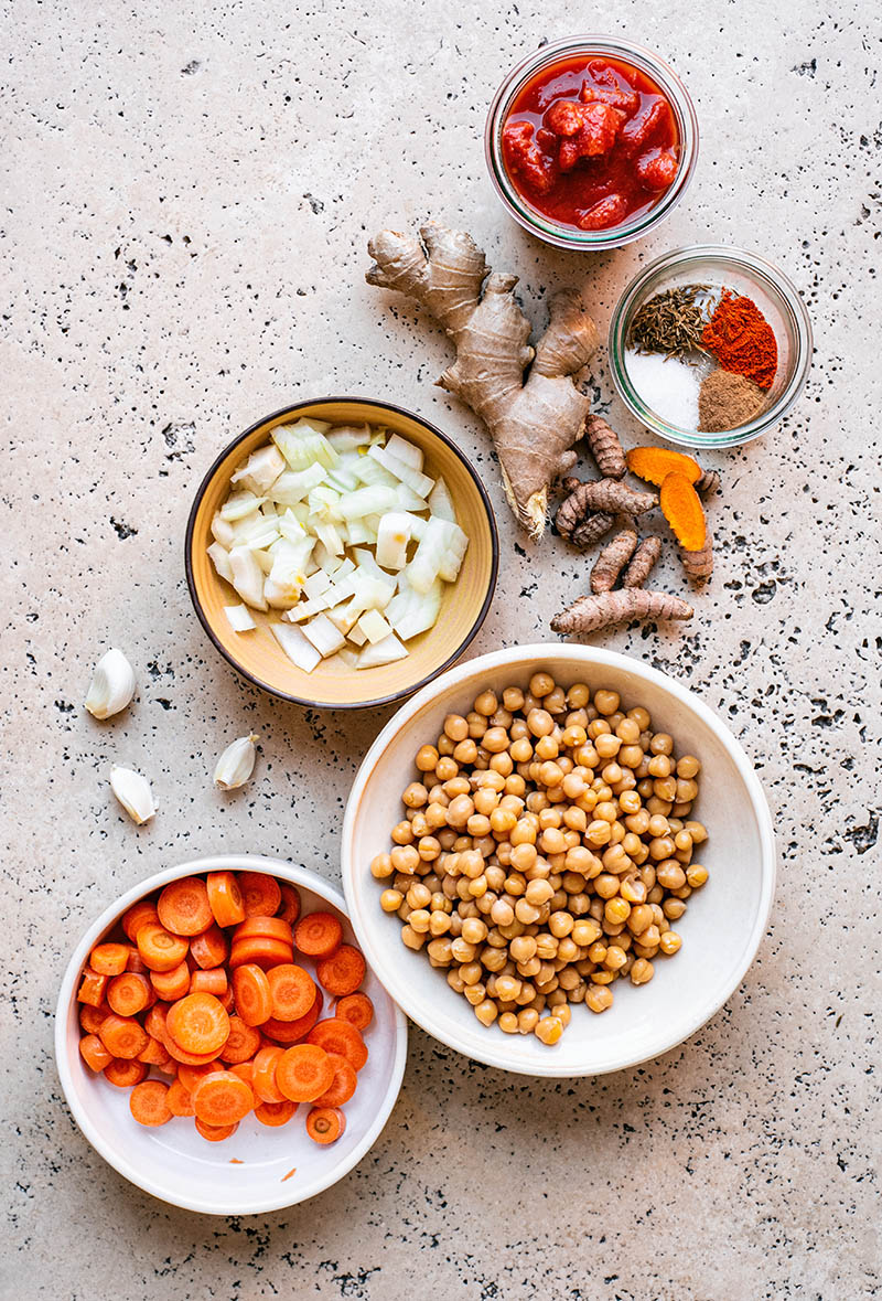 Ingredients for chickpea turmeric stew, with carrots, diced onion, and spices.