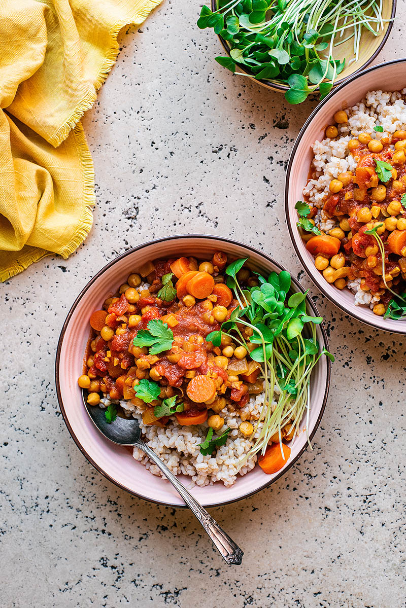 Two bowls of chickpea carrot stew with a yellow tea towel.