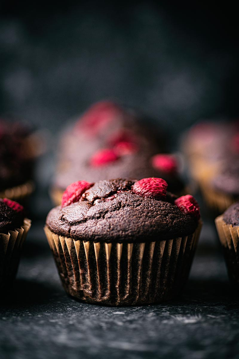 Chocolate muffins topped with raspberries on a dark background.